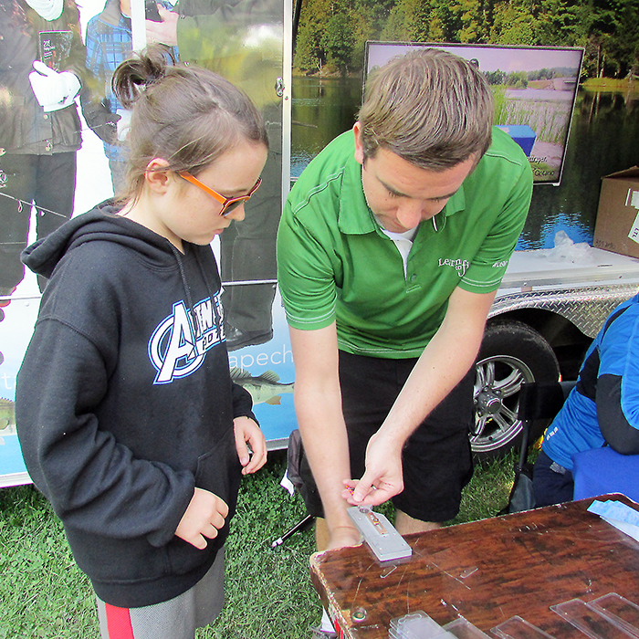Grade 5 student Cameron Rand of Sarnia gets a helping hand from Jeff Brown of the Ministry of Natural Resources and Forestry in making a fishing lure during the annual Chatham-Kent and Lambton Water Festival. The event attracted record crowds of area students during its three day run.