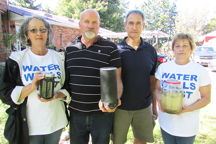 Dover resident Marc St. Pierre, left is at his wit's end with trying to get the municipality to take his water issues seriously. He recently invited Water Wells First members Cheryl Forsyth of Eberts, far left, and Yvonne Profota, also of Eberts, to his home on Bay Line to show how bad his well water has become. Pictured with them is local activist Kevin Jakubec, middle right, who is spearheading the fight to solve the Dover well problems. The group is holding black water samples from St. Pierre's tap as well as one of the white filters he has to purchase every two weeks for his filtration system.