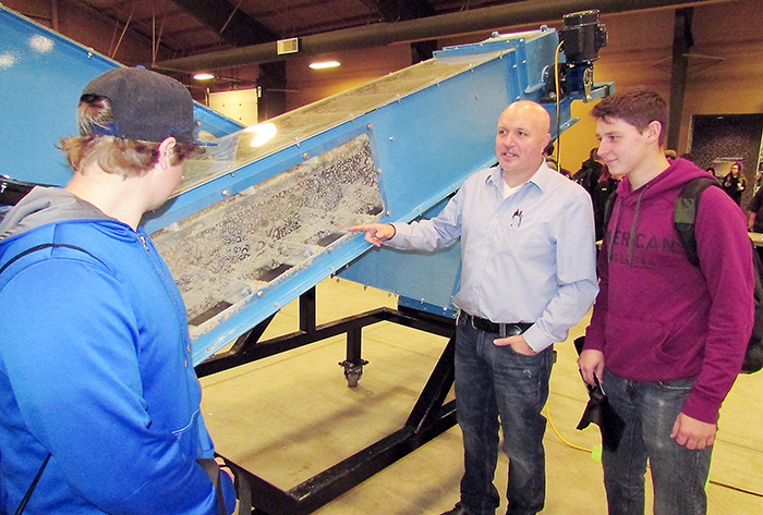 BDM Millwright's Jim Waters discusses how the company's display model dry bulk handler conveyor operates with students Robert Boccanfuso, left, and Luke Duffield at the Experience the Trades Expo that took place Nov. 16 and 17 at the John D. Bradley Centre.