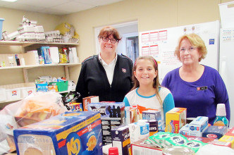 Alyah Detailleur, 10, centre, is seen with Capt. Stephanie Watkins and Bev Reeve of the Salvation Army with some of the items Alyah and her brother, Noah, 12, collected for the organization's food bank.
