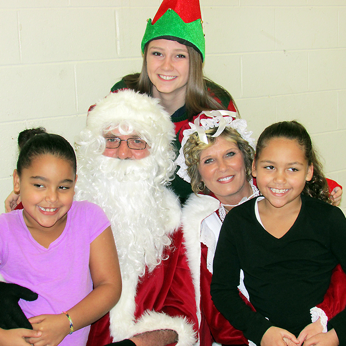 Ieesha Collier, left, and her sister Kaylin Collier, visited with Santa and Mrs. Claus at the East Side Pride Breakfast with Santa at the W.I.S.H. Centre on Saturday morning and were excited with the treat bag Santa brought for them.