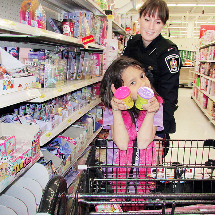 Catina Beaucage, 7, shows off some of the items she picked up during the annual Shop With A Cop event Saturday morning at Wal-Mart. With her is Const. Jennifer Jacobson of the Chatham-Kent Police Service.