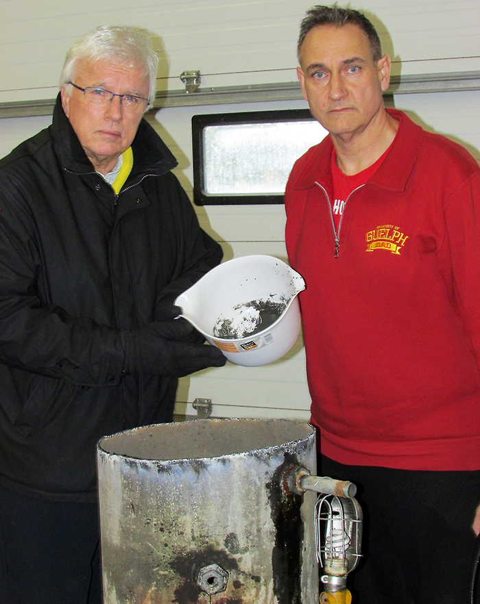 MPP Rick Nicholls gets a first-hand look at black sludge from a pressure tank of the well belonging to Dover resident Laurier Cartier, with Water Wells First spokesperson Kevin Jakubec. The toxicity of the contaminated wells are the main concern of the group.