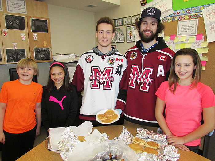 Chatham Junior B Maroon players Austin Thompson, left and Alec Mackenzie served up pancakes to a Grade 6 class for Mardi Gras at Ecole Ste. Marie on Tuesday. Students Ryan Tetrault, left, Ella-Belle Barton and Sydney Mailloux, right, lined up to meet the players and celebrate Fat Tuesday, the traditional beginning to the Catholic season of Lent.