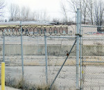 Rusted razor wire sits atop the fence surrounding the site of the former Navistar heavy truck plant in Chatham. While the company left town in 2011 and levelled the facility two years later, legal battles over employee compensation have continued.