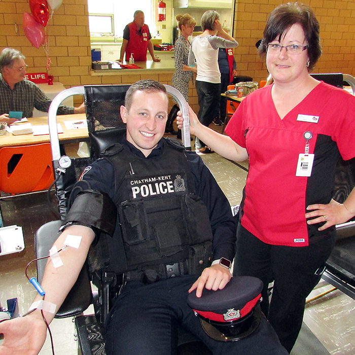 Beth Cassidy, donor care associate with Canadian Blood Services, keeps an eye on Chatham-Kent police Const. Ian Scoyne's progress as he gives blood April 12 during the Uniforms Unite to Save Lives event at the Spirit and Life Centre in Chatham. It's the seventh year of the campaign.