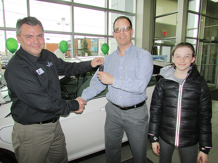 Dustin O'Neil of Essex and his daughter, Evelyn are the first customers to buy an electric car, the Ford Focus electric, from Victory Ford salesperson Mark Jackson, shown handing over the keys recently. Victory Ford is fully certified to sell and service electric cars and has the only accessible charging station in Chatham available to the public.