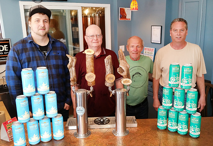 From Left, Wesley Thompson, Mike Grant, Ken Royal and Mike Dumouchelle showcase some of the canned Bayside Brewing Co. products. The Erieau-based craft brewery is expanding operations, having recently received municipal council approval on the rezoning of a property on Charing Cross Road where Bayside will can their own product, and perhaps expand brewing operations in the future.