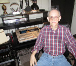 David Farquar, mastermind behind Voices In The Wind Audio Theatre, sits before his mixing station in his apartment. Voices In The Wind productions are available for download around the world.
