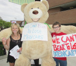 """Simon Derochie, 13, of Merlin is a teen concerned with the future of Canada's health-care system. He came out Friday to take part in the """"We Can't Bear to Lose Medicare"""" campaign that is currently touring the province. The large bear was in Chatham with the Ontario Community Health Coalition volunteers, including Kelly Jones, left, from Thamesville."""