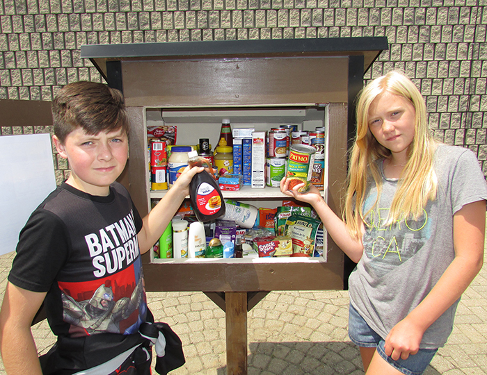 Ryan Carlson and Leah Doey, students at Queen Elizabeth Public School, deposit items into the Little Free Pantry on Adelaide Street in Chatham. Students at the school came up with the idea of a place where non-perishable food items and toiletries can be left for those in need.