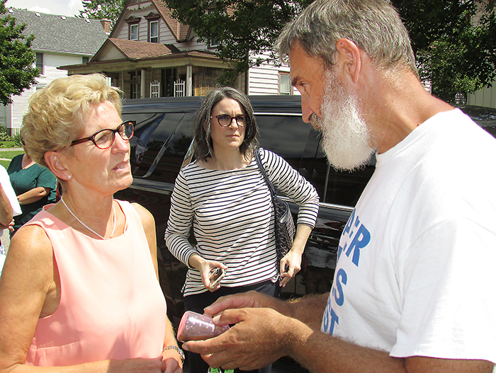 Ontario Premier Kathleen Wynne discusses sediment concerns in wells with Water Wells First representatives during a stop in Chatham on July 27.