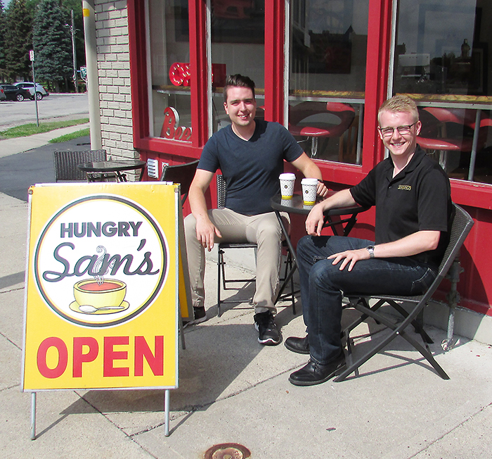 Sam Butler of Hungry Sam's/Sam's Percolator, left, and Jacob Rowe of Dennings of Chatham Funeral Home enjoy a coffee outside Butler's restaurant on Thames Street. Rowe, in a random act of kindness, posted to social media an offer by the funeral home to purchase coffee for the first 100 people to stop by Hungry Sam's on Aug. 2.